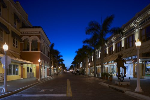 Looking northwest from the center of brick-paved First Street in downtown Fort Myers, the faint light of an early dawn glows blue at the vanishing point on the horizon, brightening the dark sky overhead. Streetlamps illuminate the 2-story building fronts while 30-foot palms lining the street are silhouetted by dawn on the horizon. The street is empty and quiet except for metal sidewalk street art of a man balancing on a unicycle.