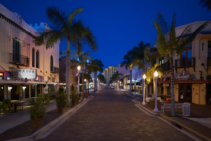 Looking southwest and down the street from the center of brick-paved First Street in downtown Fort Myers, both curbs diminish toward the vanishing point almost 1-mile distant. Streetlamps in front of 30-foot palm trees line the avenue and illuminate Capone's Coal Fired Pizza and Cabos Cantina in the foreground. The street is completely empty as the black sky overhead slowly fades to dawn. At the end of the street, and in the center of the photograph, High Point Place, a 33-story high-rise condominium, faintly catches early rays of the rising sun.
