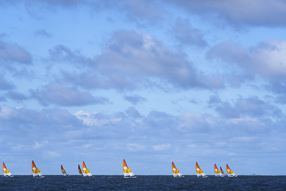 We see a landscape shot of open sky where blue clouds, offset against a deep blue sky, cap off a small strip of dark blue water in the bottom eighth of the photo. On the horizon line, intersecting sky and water, we see eleven Hobie 16 catamarans, orange and white sails piercing the skyline, spread out across the image as they race each other into the wind.