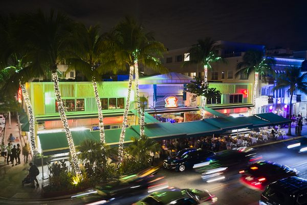 In a night drone shot, the drone hovers 30-feet on the corner of Ocean Drive and Ninth Street overlooking Mango's Tropical Café in South Beach, Miami. White Italian miniature lights decorate the trunks of 40-foot palm trees for Christmas in front of the restaurant. The palm treetops frame the top of the image. The second story façade is brightly lit in a bright greens and blues. Patrons sit outside underneath a dark green awning that runs the length of the restaurant. Headlights and taillights of passing cars blur in motion as they pass in front.