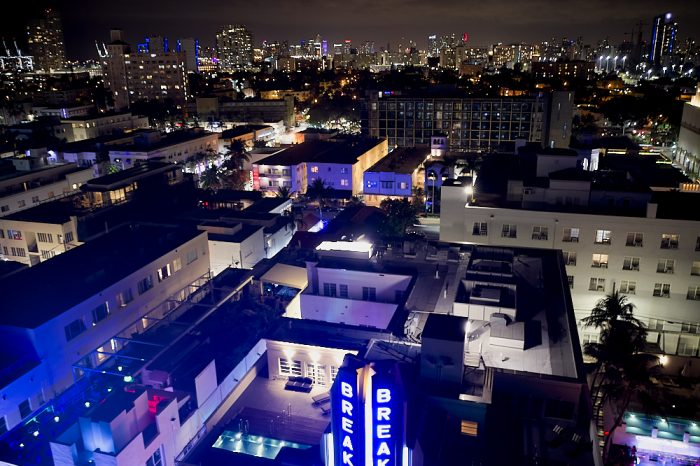 A drone, hovering 100-feet or more at night, looks west over the Breakwater Hotel's blue vertical backlit sign and roof, at the bottom of the image, to Miami's skyline over 3-miles away. Buildings and rooftops lit from the outside—many with illuminated windows—compose the lower 2/3s of this landscape image. Just beneath the black sky at the top of the image, Miami's high-rise architecture fills the horizon with hundreds of tiny neon and window lights from the buildings on the skyline.