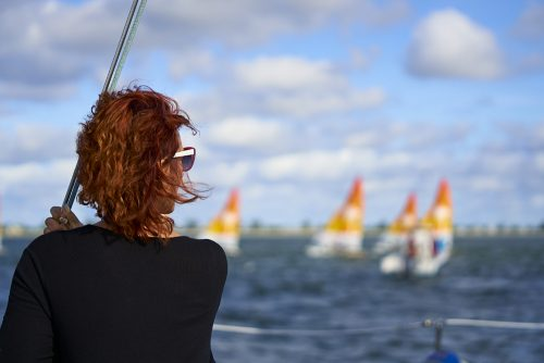 Sitting on the observation catamaran I look abeam over the shoulder of a woman with deep red hair and a dark black sweater who is on the left one-third of the image. The right side of her face turns toward the center of the image as she watches a sailboat race. We see the edge of her red framed sunglasses and white temple arm extending back and wrapping over her right ear. Her red hair blows away from me, onto her face. The center and right one-third of the image includes four Hobie 16 sailboats with white and orange sails, racing in the Hobie 16 World race off of Captiva Island, Florida, under a white cloud and bright blue sky. The sailboats and sky are heavily blurred because the image focuses on the woman.