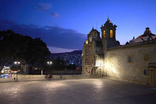 Overlooking the Plaza de la Danza with the Basilica of Our Lady of Solitude on the right side of the image. A dark blue twilight sky frames the silhouetted trees in the back of the plaza and twinkling lights on the nearby mountain in the background. Young friends gather to talk on the far side of the plaza underneath the lamp light. Photo is taken from Avenue Jose Maria Morelos.