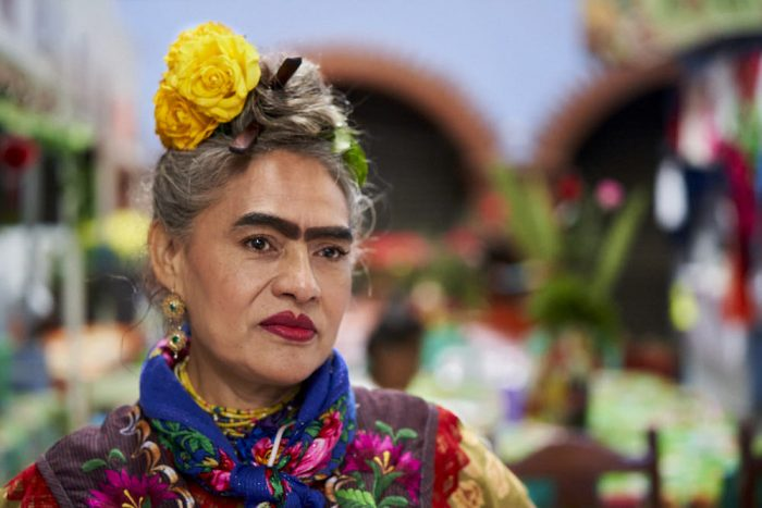 Horizontal photo of a woman working at a restaurant inside the public market in Ocotlan de Morelos. She wears traditional dress and apron embroidered with pink and red flowers and green stems and leaves. Her navy-blue scarf, wrapped around her neck and knotted in front, displays a similar red and pink flower design. Long, thick heavily mascaraed eyebrows almost converge at the bridge of her nose, framing dark brown eyes. She has traced her full lips, heavily applied with bright red lipstick, with an even darker red outline. She wears her black and gray hair up on top of her head, pinned with large fresh yellow flowers.
