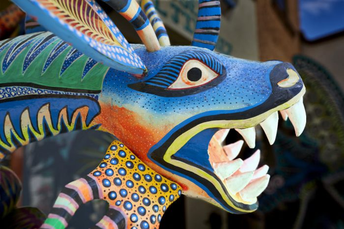Horizontal photo of an albrijes carving—brightly colored Mexican folk-art sculptures—of a fantastical mythical multicolored dragon head. We see the head from the right side: blue at the top and bright orange on his neck. Large black eyes, surrounded by white, protrude from the top of his head, just in front of large rabbit-like ears and multicolored horns. Tiny black and white dots decorate his blue face. Large fangs angle from the top and bottom of his wide-open jaws. Yellow, black, and blue strips of paint outline his mouth. This angry dragon is ready to attack.