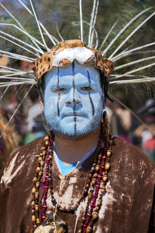 Vertical portrait of man dressed for the carnival celebration of lent in the village of Tilcajete, Mexico. The man has painted his face in light-blue paint, which covers his forehead down to his chin. The blue paint also covers his short mustache and beard. He has painted three blue vertical lines down his face, across his eyes and cheeks; and down the middle of his forehead, nose, and chin. He wears a paper-mache jaguar head mask like a hat on the top of his head. About 35-peacock feathers protrude from the back of his head in a 180-degree arc. Over the top of a brown and white tie-dyed shirt, red-dyed corn and brown acorn necklaces hang around his neck.