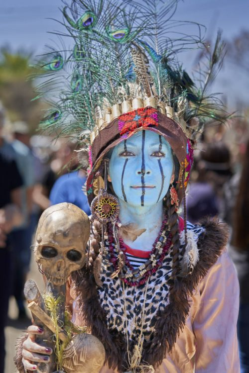 Vertical portrait of woman dressed for the carnival celebration of lent in the village of Tilcajete, Mexico. She has painted her face in light-blue paint, which covers her forehead down below her neck. Three blue vertical lines run down her face, forehead, eyes, cheeks, and chin. On top of her head, an American Indian-style headdress sprouts peacock feathers which stick up into the sky. Large multicolored earrings dangle from her ears. Four beaded necklaces drape over her jaguar-print shirt, underneath a long sleeve V-neck blouse with a faux fur collar. She carries a small human skull on a stick in her right hand.