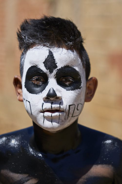 Vertical portrait of a young boy costumed for the carnival celebration of lent in the village of Tilcajete, Mexico. His torso and shoulders are covered in dark black body paint, which glistens with sweat in the overhead sun. He has painted his face to look like a skull—white face paint with large black circles around each of his eyes. A triangular dash of black covers the tip of his nose. Thin vertical lines, drawn to appear as large teeth, cover the bottom of his cheeks and mouth. His hair is cut closely on the sides but sticks up in a compact black tousled bristle on the top of his head.