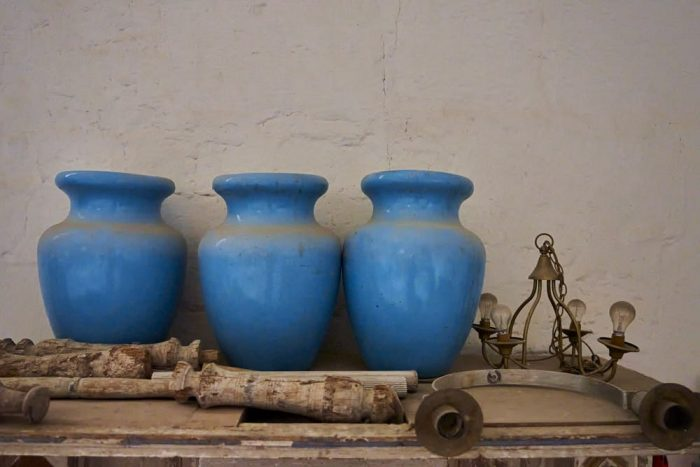 Horizontal photo of four large, light blue ceramic urns, 18-inches at the center diameter, that appear to have been abandoned in the church of Saint John the Baptist, located in San Juan Bautista Coixtlahuaca, Mexico. The dusty urns lean against a stucco wall, askew, on a table along with several discarded candleholders and an old hanging chain light fixture with four dirty bare lightbulbs.